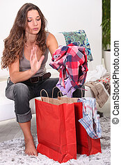 Woman sat on sofa looking through her shopping bags