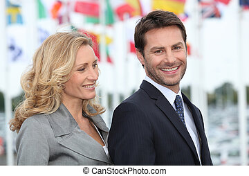 Couple of executives with flags in the background