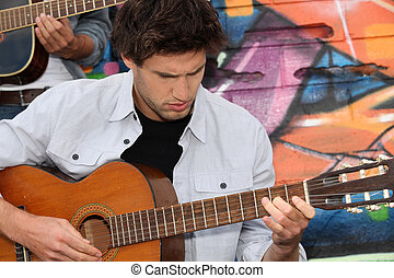 Musician with guitar in front of painted wall