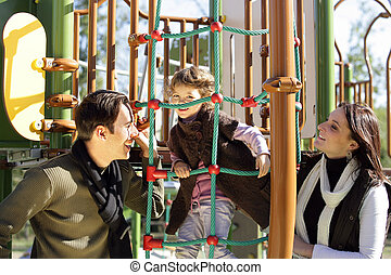 Little girl playing in a park with parents