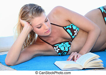Blond woman reading a book whilst sunbathing