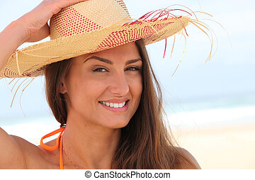 Woman on the beach with straw hat