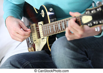 Closeup of a man playing a guitar