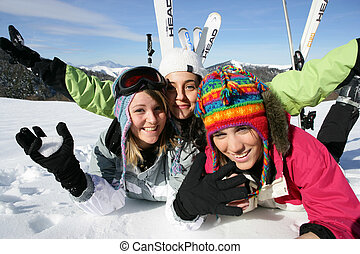Three female friends laying in the snow
