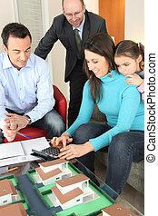 Family sat around model housing