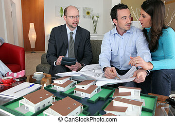 Property salesman sat with couple