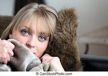 Woman warming herself up under blanket