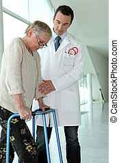 Doctor helping elderly patient with walking frame