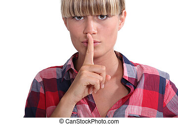 Young woman with a blunt fringe holding her finger to her...