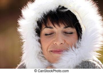 Woman keeping warm by wearing furry hood