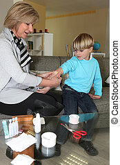 Woman sticking a plaster on a child's arm