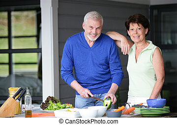Middle-aged couple cooking outdoors together