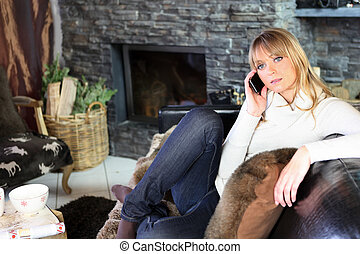 Woman speaking on her mobile phone in her cozy living room
