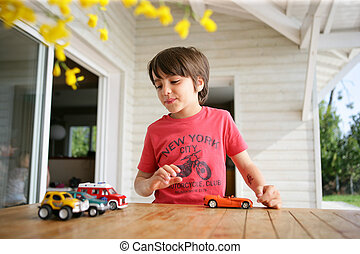 Young boy playing with his toy cars