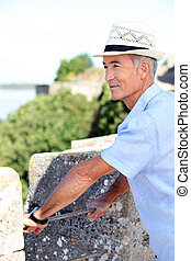 Grey-haired man visiting port town