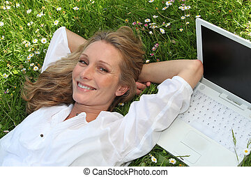 woman with computer in a field