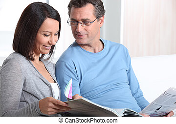 Couple reading sat on a couch