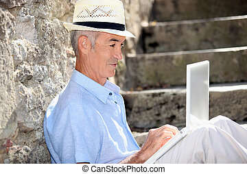 Elderly man sat on steps with laptop