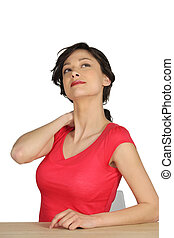 Woman sitting at a desk rubbing her neck