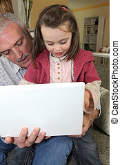 Grandfather with granddaughter and computer