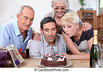 woman blowing birthday candles in family