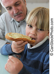 Boy eating bread with his grandfather