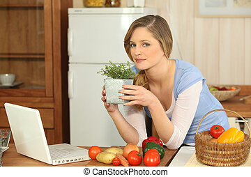 Woman smelling herbs in the kitchen
