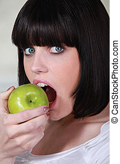 Brunette woman biting apple