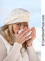 Woman drinking hot beverage to warn herself up