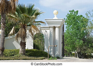 Entrance Gates - Stately white entrance gates with palm...