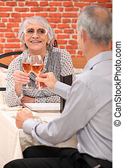 Mature couple toasting with rose wine