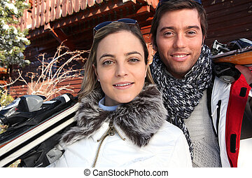 Couple on ski holiday stood by chalet