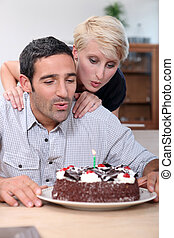 Couple blowing candle