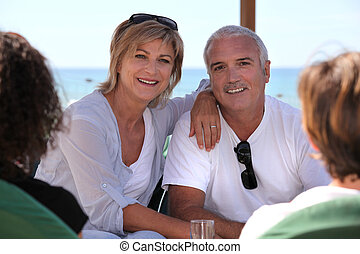 Mature couple sitting on a bar terrace