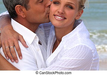 man kissing his blonde girlfriend at beach