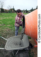 Man pouring cement into wheelbarrow