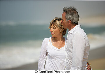 Married couple dressed in white taking a walk along the beach