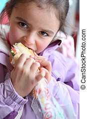 Little girl eating sandwich