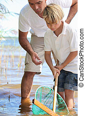 Father teaching son to fish with net