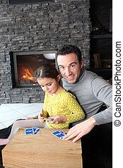 Father and daughter playing card game by fire place
