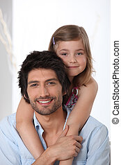 Young girl riding piggy-back on her father's back