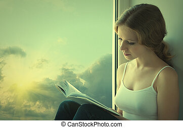 beautiful young woman reading a book while sitting at a window in the sky and sunset