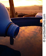 rain barrels - Water dripping from a motor oil bottle into a...