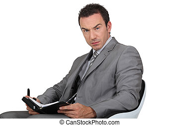 Man in suit writing in diary