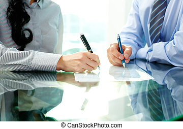 Signing agreement - Two business people signing a document