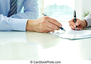 Signing contract - Two business partners signing a document