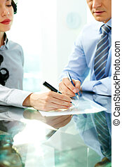Signing a paper - Two business partners signing an agreement