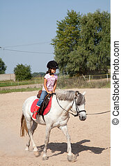 Little Girl Taking Horseback Riding Lessons - Little girl...