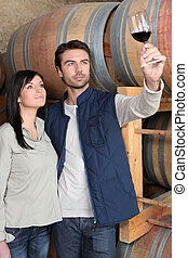 couple tasting wine in a cellar