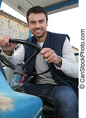 Young farmer driving a tractor